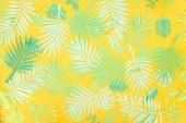 pohled shora na papír řezané zelené tropické listy na žlutém pozadí s prostorem pro kopírování