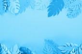 Fotografie Obere Ansicht von Papierblättern auf blauem minimalistischem Hintergrund mit Kopierraum