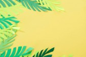 top view of paper cut green tropical leaves on yellow bright background with copy space