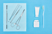top view of set with dental tools near toothpaste and toothbrush isolated on blue