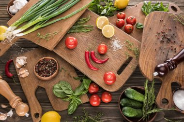 top view of cutting boards, cherry tomatoes, salt, garlics, cucumbers, chili peppers, pepper mill, salt mill, lemons and spices
