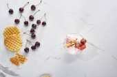 Nejlepší pohled na lahodnou zmrzlinu s Vafle a jahodami v blízkosti třešní na mramorové šedé pozadí