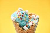 Fotografie zblízka pohled na lahodnou sladovou modrou zmrzlinu s marshmallowy a posypy v křupavých vaflových kužlech izolovaných na žluté