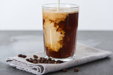 milk pouring into ice coffee in glass on napkin with coffee grains isolated on white