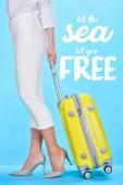Fotografia vista ritagliata della donna che tiene manico di borsa da viaggio gialla su sfondo blu con lasciare che il mare si imposta illustrazione gratuita