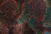 Fotografie abstrakter Hintergrund aus silbrig glänzender, strukturierter Lumpenfolie mit farbenfroher Beleuchtung