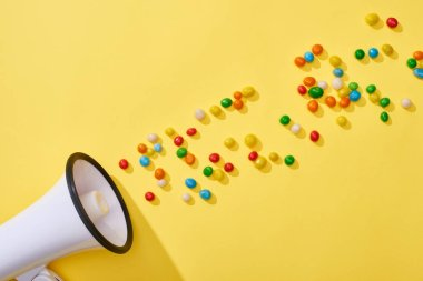 top view of loudspeaker with colorful candies on yellow background