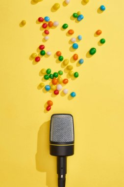 Top view of microphone with candies on bright and colorful background stock vector