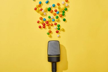 Top view of microphone and candies on bright and colorful background stock vector