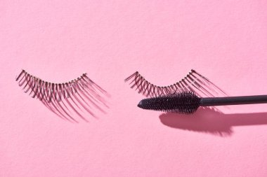 top view of false eyelashes and brush on pink background