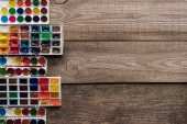 top view of colorful paint palettes on wooden brown surface with copy space