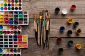 barevné palety s barevným nátěrem na dřevěné hnědé ploše s štětci a kvaše
