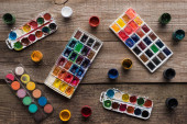 top view of colorful paint palettes on wooden brown surface with gouache