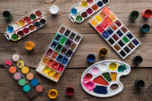 Photo top view of colorful paint palettes and gouache on wooden brown surface