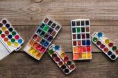horní pohled na palety akvarových barev na dřevěné hnědé ploše