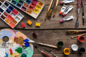 top view of colorful paints and drawing tools on wooden surface with copy space
