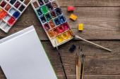 Zobrazení barevných palet, štětců a prázdného panelu náčrtku na dřevěné ploše shora