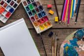 felülnézet festékpaletták, ecsetek, színes ceruza és az üres vázlat pad fa felületen