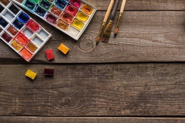 top view of watercolor paint palettes and paintbrushes on wooden surface with copy space