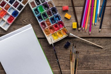 Top view of colorful paint palettes, paintbrushes, color pencils and blank sketch pad on wooden surface stock vector