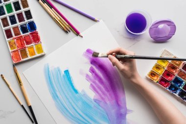 Cropped view of artist drawing purple and blue watercolor brushstrokes on white paper on marble white surface stock vector