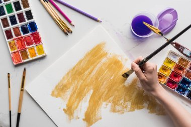 Cropped view of artist drawing yellow watercolor brushstrokes on white paper on marble white surface stock vector
