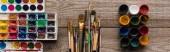 barevné palety s barevným nátěrem na dřevěné hnědé ploše s štětci a kvaše, panoramatický záběr