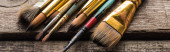 close up view of old paintbrushes on wooden brown surface, panoramic shot