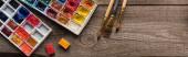 horní pohled na palety akvarel na dřevěné hnědé ploše s štětci, panoramatický záběr