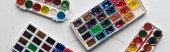 Photo top view of colorful paint palettes on marble white surface, panoramic shot
