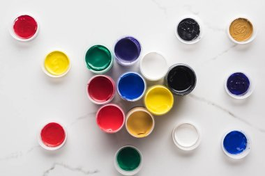 Top view of multicolored gouache paints on marble white surface stock vector