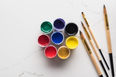 Top view of multicolored gouache paints and paintbrushes on marble white surface stock vector
