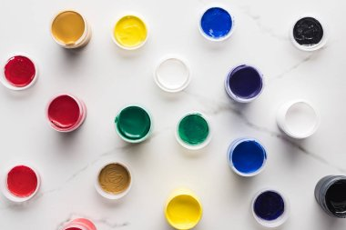 Top view of multicolored gouache paints on marble textured surface stock vector
