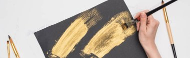 partial view of artist drawing brushstrokes with golden paint in black paper on marble surface, panoramic shot