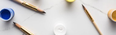 Top view of colorful gouache paints and scattered paintbrushes on marble white surface, panoramic shot stock vector