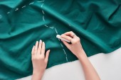 top view of seamstress drawing on colorful fabric with chalk on white background