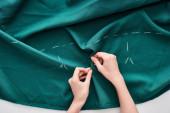 Fotografia vista dallalto della sarta cucito tessuto colorato con ago su sfondo bianco