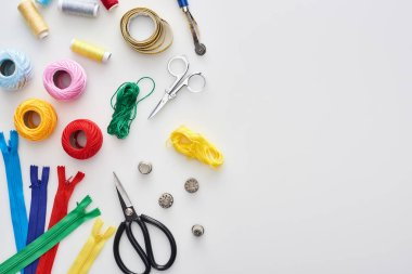 top view of zippers, scissors, thimbles, threads, knitting yarn balls, bobbins, tracing wheel, measuring tape on white background