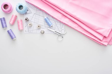 top view of fabric, knitting yarn balls, sewing pattern, scissors, thimbles, bobbins and threads on white background