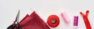 panoramic shot of colorful threads, knitting yarn ball, fabric, scissors and zipper on white background