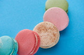 close up view of multicolored tasty French macaroons on blue bright background