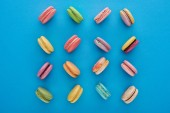 Fotografie flat lay with sweet multicolored delicious French macaroons on blue bright background