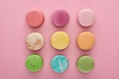 flat lay with multicolored delicious French macaroons on pink background
