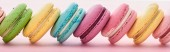 row of delicious French macaroons of different flavors on pink background, panoramic shot