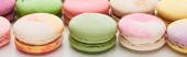 close up view of sweet colorful French macaroons of different flavors on white background, panoramic shot