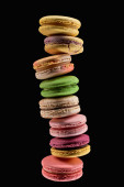 stack of delicious fresh French macaroons of different flavors isolated on black