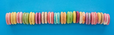 top view of multicolored delicious French macaroons in row on blue bright background, panoramic shot