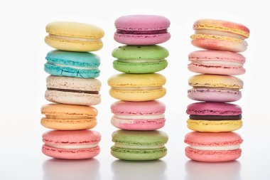 three rows of sweet multicolored French macaroons of different flavors on white background