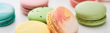 close up view of sweet French macaroons of different flavors on white background, panoramic shot
