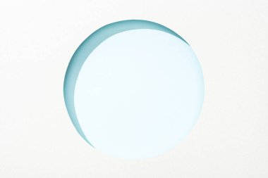 Cut out round hole in white paper on light blue background stock vector